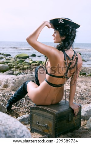 Half-dressed pirate woman sitting on the beach and looks afar - stock photo