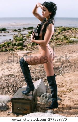 Half-dressed pirate woman standing on the beach and looks afar