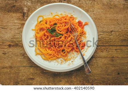 half eaten plate of a spaghetti al pomodoro served with parmesan cheese and fresh basil