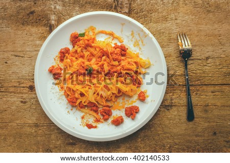 half eaten plate of a tagliatelle with bolognese sauces served with parmesan cheese and a fresh basil