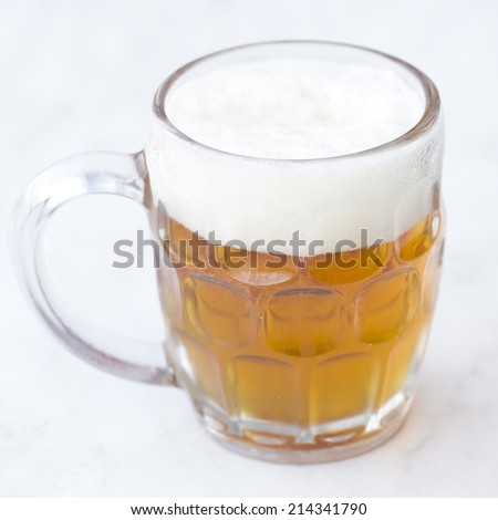 half empty golden beer glass jar isolated on a grey background.