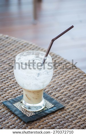 Half empty  ice coffee glass on the table. - stock photo