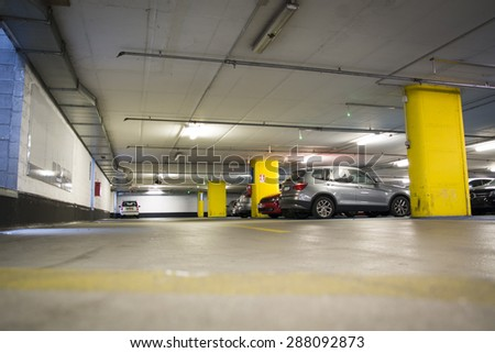 Half empty underground garage or parking lot, with a few cars