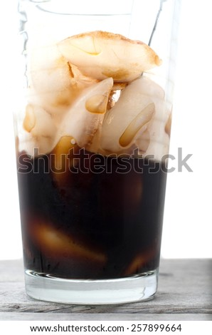 Half empty Vietnamese ice coffee glass on a wooden table against white background - stock photo