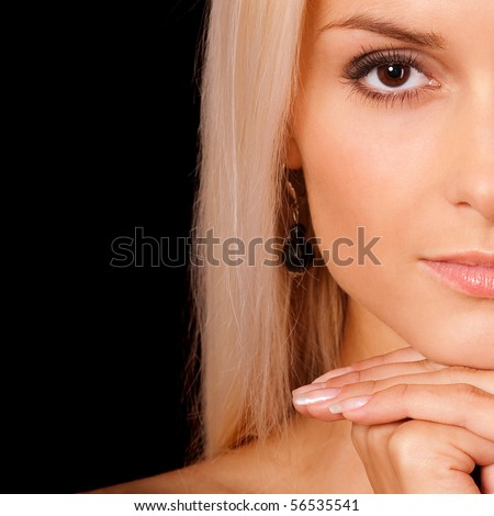 Half face charming blonde, it is isolated on black background. - stock photo