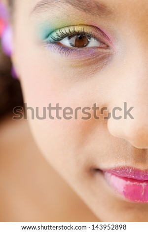 Half face close up beauty portrait of an attractive young girl looking up and smiling at camera while wearing a rainbow color eye shadow and glossy lips with perfect skin. - stock photo
