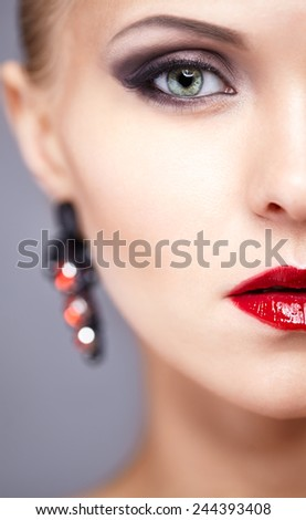 Half face close-up portrait of young woman with red earrings  - stock photo