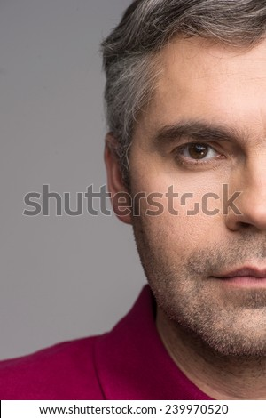 half face of adult man on grey background. grey haired male looking into camera - stock photo