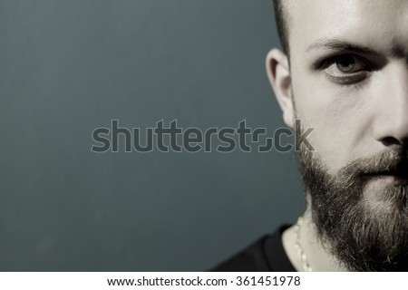 Half face of cool man with green eye and beard looking camera - stock photo