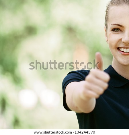 Half face of smiling beautiful young woman in dark blouse lifts thumb upwards, against green of summer park. - stock photo