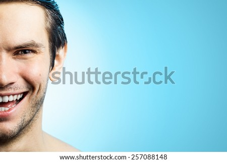 Half face of young handsome happy man on sky blue background. - stock photo