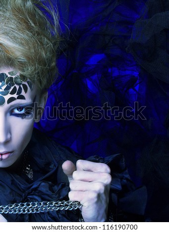 Half face of young man in dark creative image - stock photo