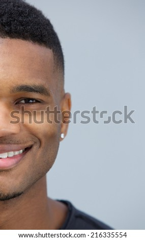 Half face portrait of a smiling man posing against gray background