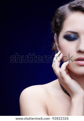 half face portrait of young beautiful brunette woman with eyes shut posing in beads with manicured fingers - stock photo