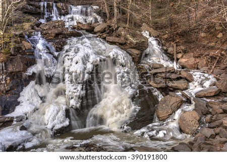 Half frozen Bastion Falls beside Route 23A on Lake Creek, about 1/2 miles downstream of Kaaterskill Falls in the Catskills Mountains of New York. (HDR) - stock photo