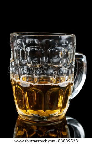 half-full glass of beer isolated on a black background