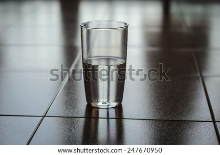 Half Full or Half Empty? Glass half filled with plain water put on a floor shot low-key with shadow dark background. Reflection of glass is visible on the floor. - stock photo