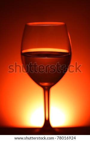 Half fulled wine glass in red background