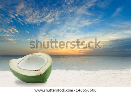 Half green coconut on white sand beach in Thailand - stock photo