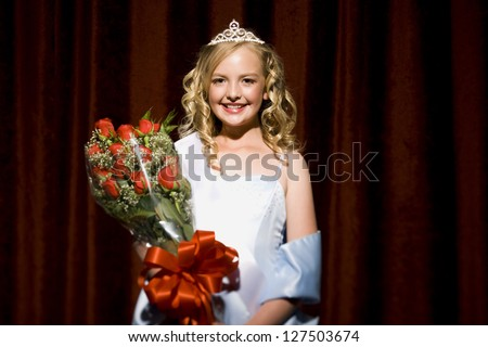 Half length of a beauty pageant winner smiling and holding roses - stock photo
