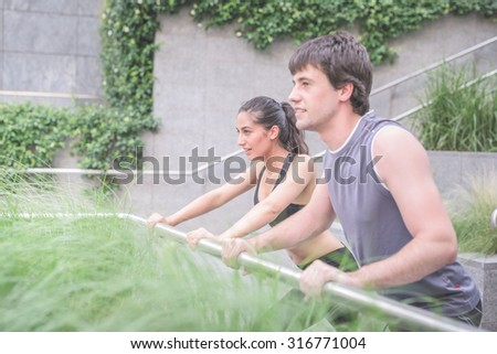 Half length of a couple of handsome caucasian sportive man and woman stretching leaning on a handrail, both overlooking right, smiling - sportive, fitness, health concept - stock photo
