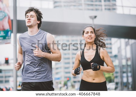 Half length of a couple of young handsome caucasian man and woman running into the streets of the city, both overlooking left - sportive, fitness, healthy concept - stock photo