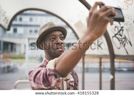 Half length of a young handsome afro black man holding a smart phone, taking a selfie, smiling - social network, vanity, technology concept - stock photo