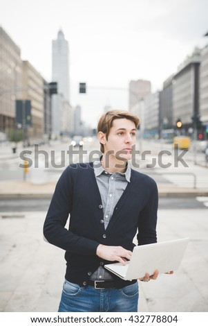 Half length of a young handsome caucasian contemporary businessman standing on the street using a notebook overlooking left - technology, network, business, finance concepts - stock photo