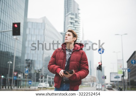 Half length of a young handsome caucasian contemporary businessman walking through the city using a tablet overlooking right - technology, network, business, finance concepts - stock photo