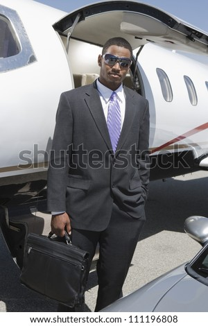 Half-length of businessman getting out from a jet - stock photo