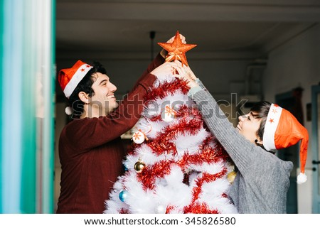 Half length of couple of young handsome caucasian man and woman decorating christmas tree, putting tree topper star - christmas, holiday concept - stock photo