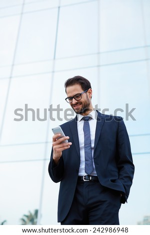 Half length of happy businessman reading text message on cell phone with one hand in a pocket - stock photo