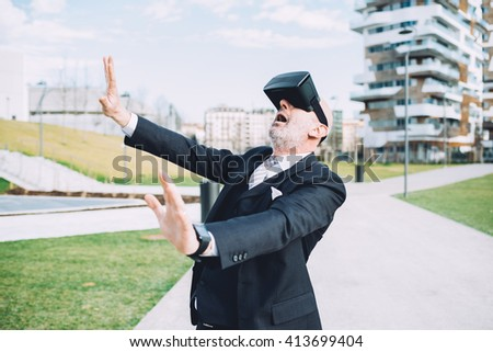 Half length of middle age caucasian business man using smart watch and 3D viewer, looking upward - futuristic, multitasking, technology concept - stock photo