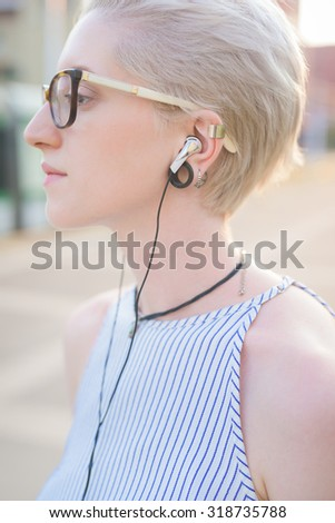 Half length of the profile of a young handsome caucasian blonde italian designer listening music with earphones - wearing striped shirt - music, relaxing, technology concept