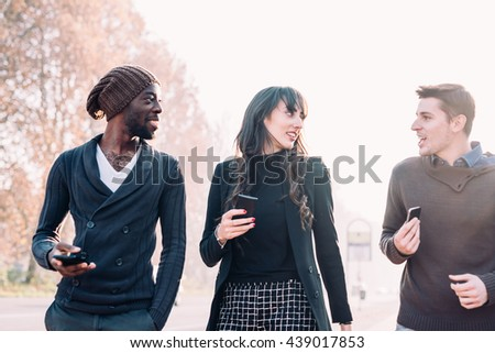 Half length of three multiethnic woman and men friends walking outdoor in city back light, chatting and holding smart phone - friendship, social network, conversation concept