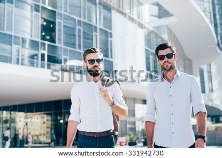 Half length of two young bearded blonde and black hair modern businessman, walking in the city backlight, one looking in camera, the other overlooking right - working, successful concept - stock photo