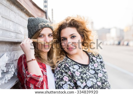 Half length of two young curly and straight blonde hair caucasian woman leaning on a wall, one playing with the other's hair, use it in shape of mustache - youthful, carefree, friendship concept - stock photo