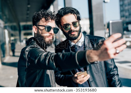 Half length of two young handsome caucasian bearded brown hair businessmen outdoor in the city taking a selfie, using a smartphone handhold - vanity, communication, social network - stock photo