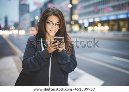 Half length of young beautiful caucasian brown hair woman with glasses tapping the screen of a smart phone hand hold in the city evening - technology, social network, communication concept