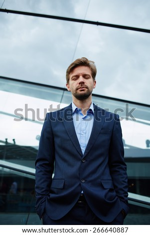 Half length of young businessman standing with closed eyes and hands in his pockets against office building, peaceful man having big hope looking confident