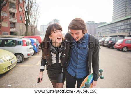 Half length of young caucasian woman and man with a skate and moustache posing walking trough the streets of the city hugging and listening to music - carefreeness, friendship, love, youth concept - stock photo
