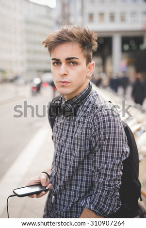 half length of young handsome alternative man leaning on a post with central labret and nostril piercing listening music with headphones and smartphone connected online -  technology concept