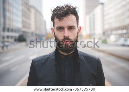 Half length of young handsome black hair caucasian modern businessman posing in the city, looking in camera, serious - pensive, thoughtful, thinking future concept - stock photo