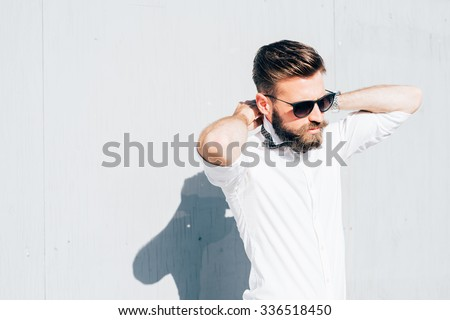 Half length of young handsome blonde caucasian modern businessman posing leaning against a wall, overlooking left, wearing bow tie - business, successful concept - stock photo