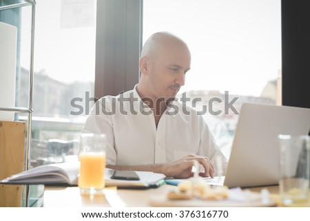 Half length of young handsome caucasian bald business man sitting in a bar using a laptop looking downward and tapping the screen, smiling - working, happy, busy concept - stock photo