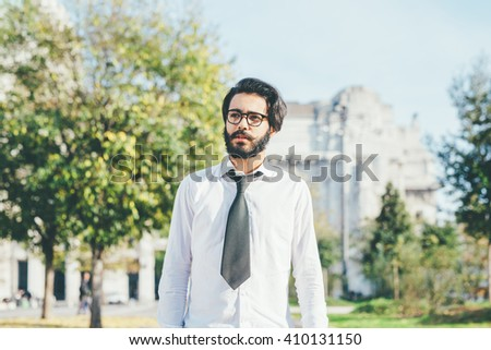 Half length of young handsome Caucasian black hair bearded businessman walking outdoor in the city, overlooking - pensive, thoughtful, serious concept. - stock photo