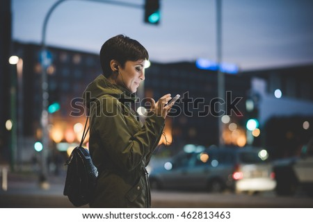 Half length of young handsome caucasian brown straight hair woman holding a smartphone looking down the screen in city night, face illuminated by screen light - technology, communication concept