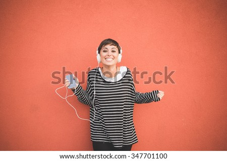 Half length of young handsome caucasian brown straight hair woman listening music with headphones leaning against a wall, looking in camera smiling, holding smartphone - technology, music concept - stock photo