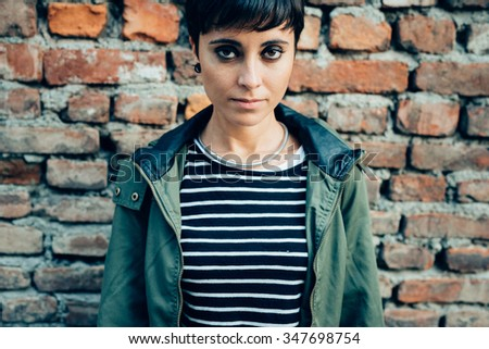 Half length of young handsome caucasian brown straight hair woman posing leaning against a wall, looking in camera, pensive - serious, thoughtful concept - stock photo