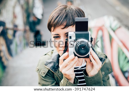 Half length of young handsome caucasian brown straight hair woman taking a photo with vintage camera - artist, creative concept - stock photo